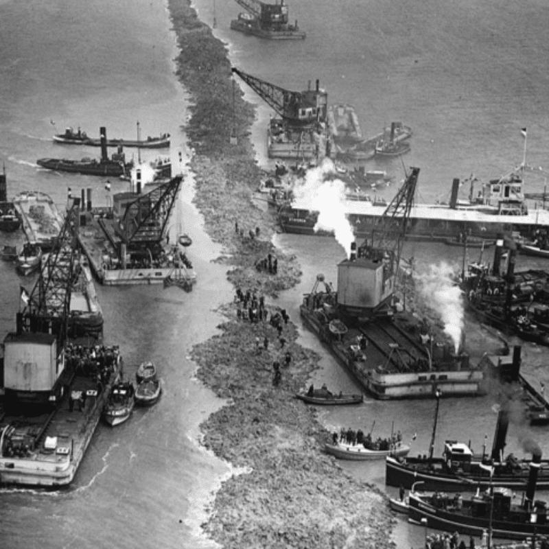 Dies ist ein altes Foto vom Bau des Afsluitdijk im Jahr 1920. Der Bau des Afsluitdijk hat gerade hier begonnen. Sie sehen eine Sandbank auf beiden Seiten der Segelboote.