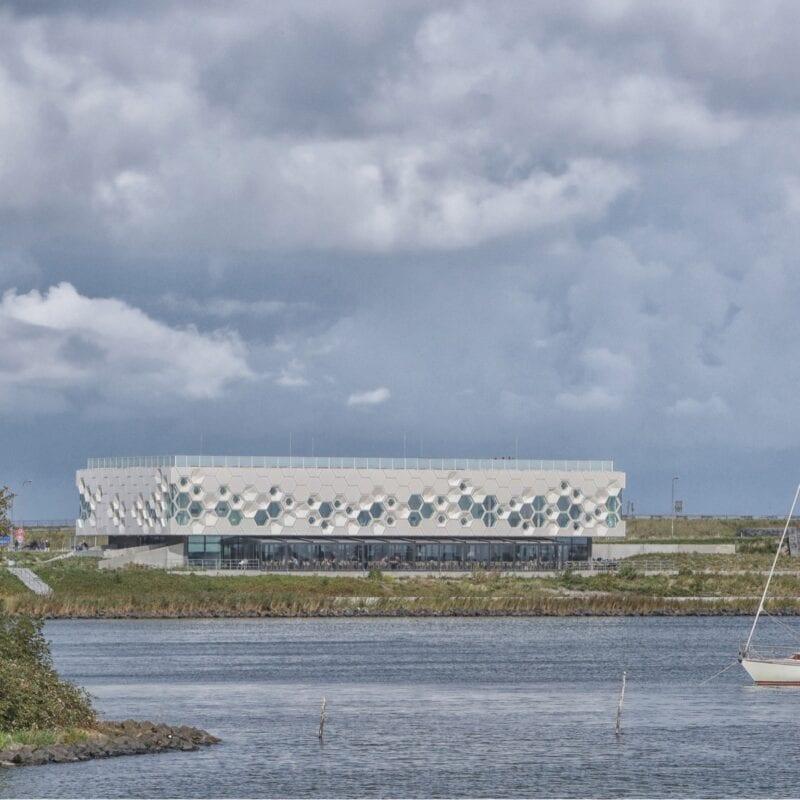 Foto des Afsluitdijk Wadden Centers auf der Rückseite. Sie sehen Wasser dafür. In diesem Wasser befindet sich ein Segelboot.