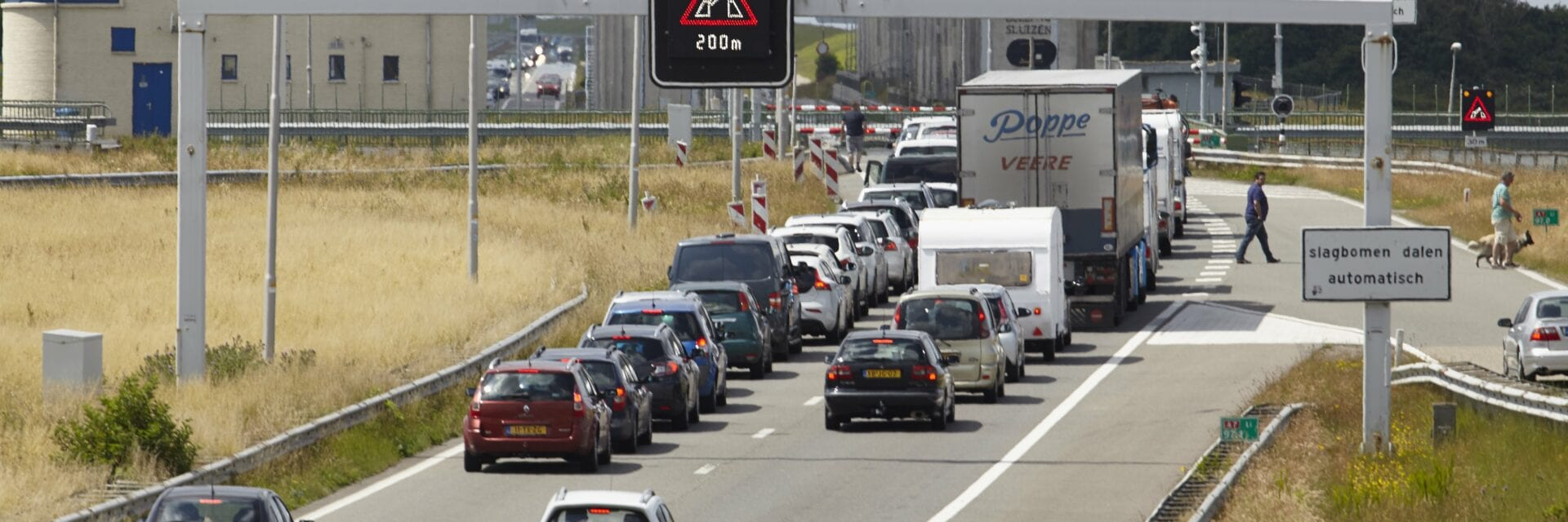 Verkehr auf dem Afsluitdijk durch eine offene Brücke. An den Schleusen steht eine lange Reihe von Autos und Lastwagen.