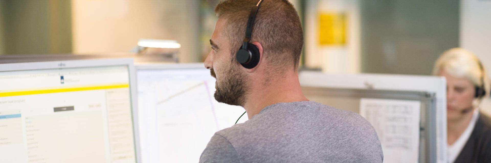 Mitarbeiter Loket Afsluitdijk. Ein Mann sitzt mit einem Computer und einem Headset an einem Schreibtisch.
