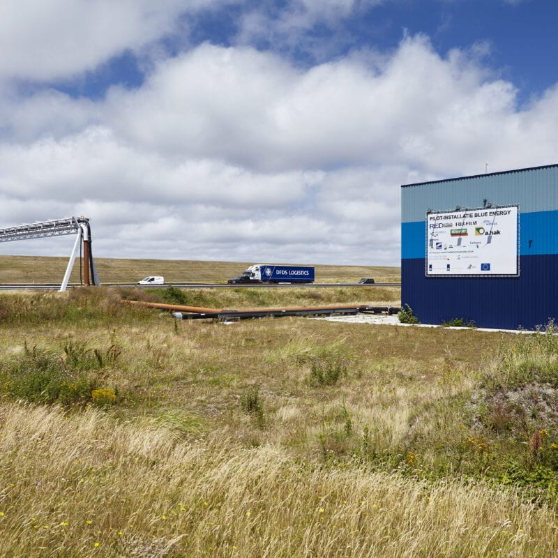Blue Energy building. In the photo you see a grassy landscape. On the right is a blue building with a white banner. Further at the back you see a road with a gray pole above the road.
