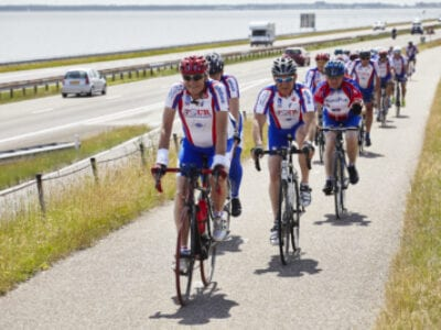We see a peloton of cyclists riding on the path next to the road on the Afsluitdijk.