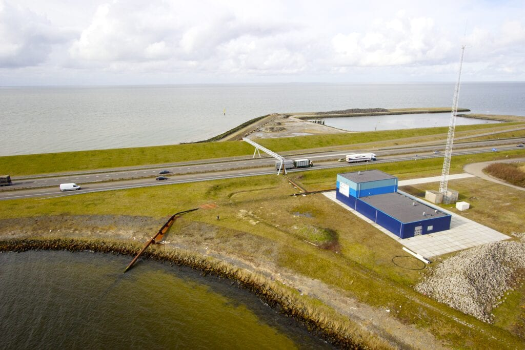 Building of Blue Energy. We look from above on the road and the grass of the Afsluitdijk. On the right we see a blue building of Blue Energy.