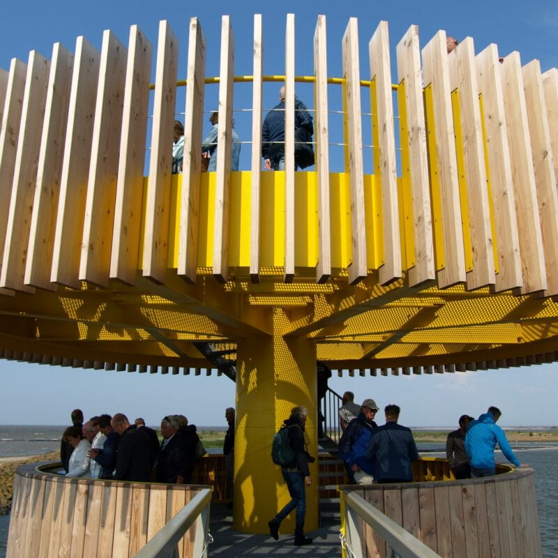 We look out over the water of the Wadden Sea. In the middle of the photo we see the experience point at Den Oever. This is a yellow tower with two discs on top of each other. We are at the level of the first disk and look at the top disk. There are many people on the tower.
