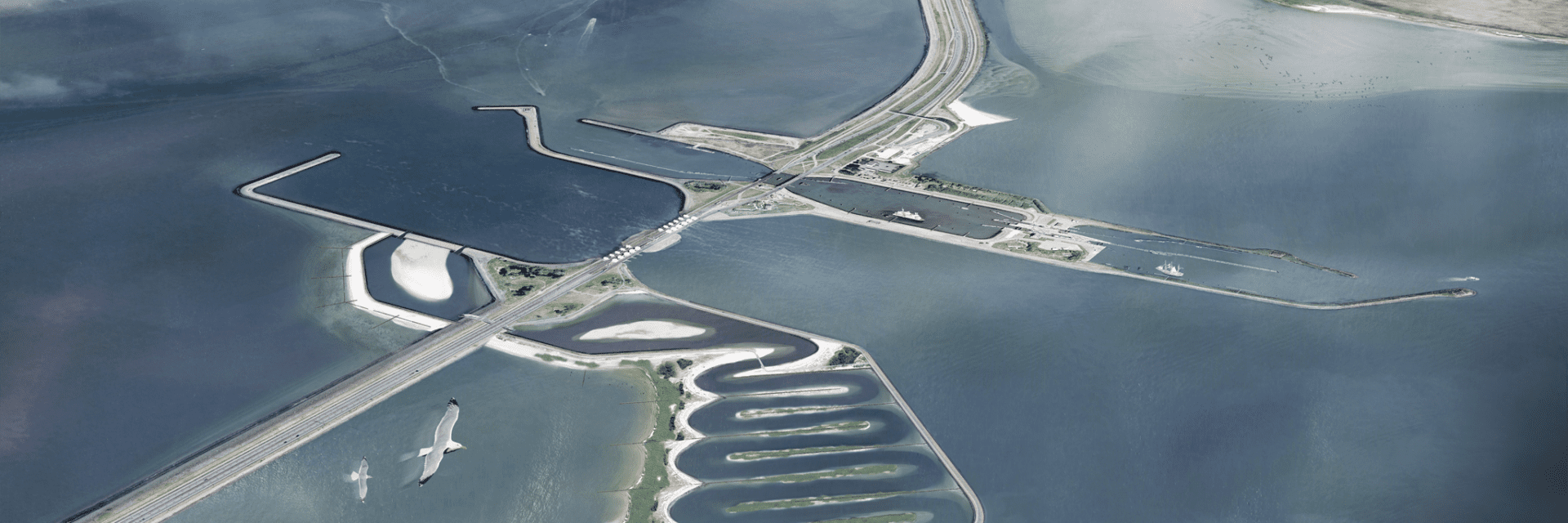 Impression of the Fish Migration River. You see a drawn version of the Afsluitdijk. The Fish Migration River has been drawn in the Afsluitdijk. This is a meandering river, outlined with strips of soil. On the side of the Waddenzee you will see an estuary harbor. In this image, the green is also drawn near the dike.