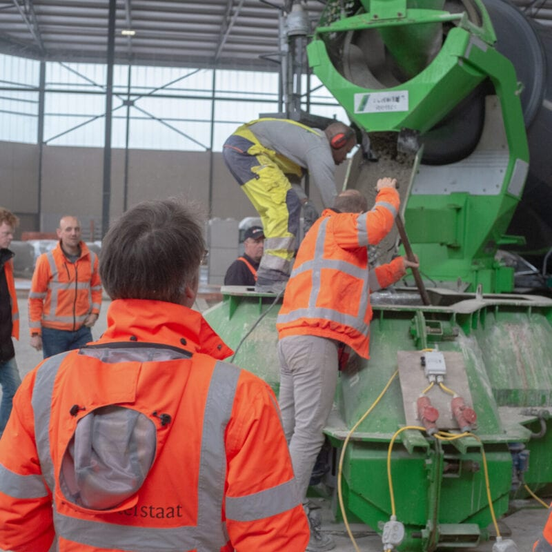 In this picture you see people getting concrete out of a wagon. They wear orange safety clothes.